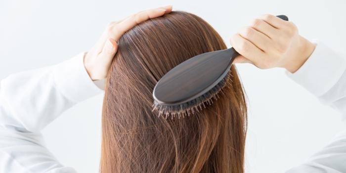 髪の毛をとかす女性